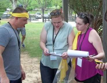group looking at GPS and clipboard preparing for scavenger hunt