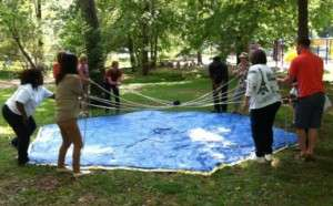 a challenge-based team building activity with a ball and ropes