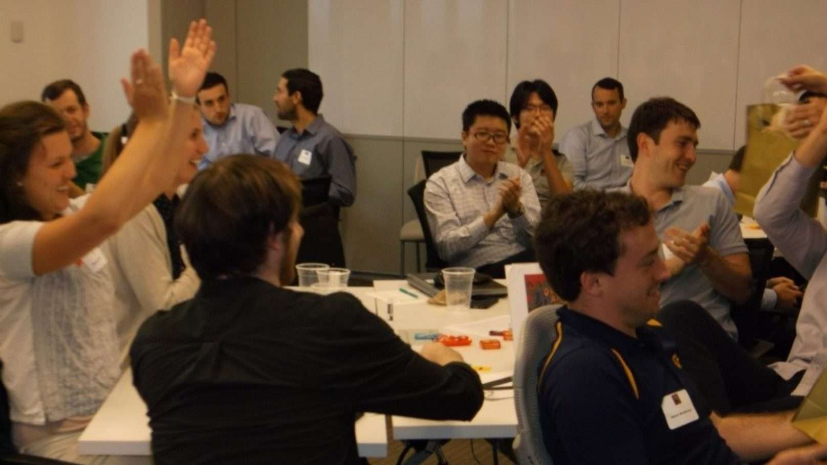 group clapping at an indoor corporate team building program